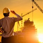 Silhouette engineer wear a helmet at construction site with crane background and sunset